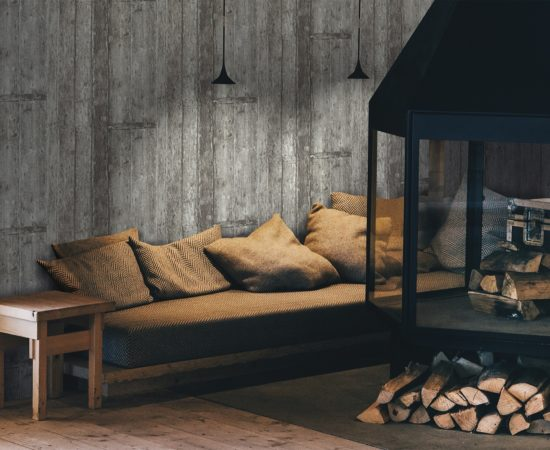 Cosy fireplace with pillows and tree logs ready to get relaxed at